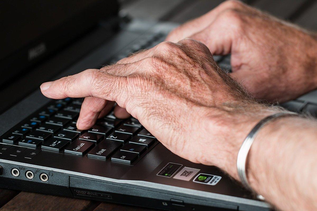 Seniorenhände auf dem Laptop