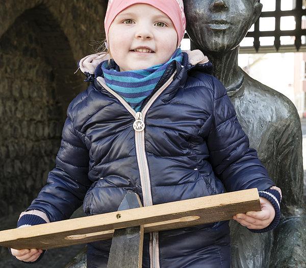 Klappermädchen auf dem Schoß der Bronzefigur des Klapperjungen