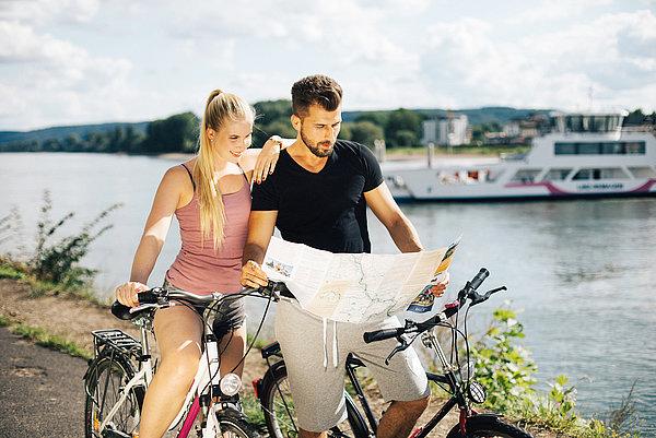 Junges Pärchen auf Rädern im Sonnenschein am Rhein die eine Radkarte lesen