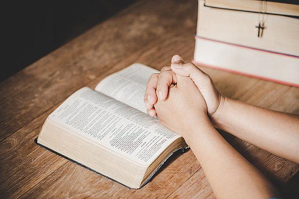 Betende Hände über dem Gebetbuch