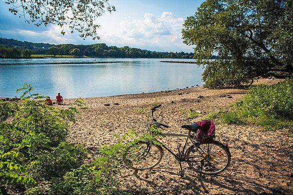 abgestelltes Fahrrad am Rheinufer im Sonnenschein