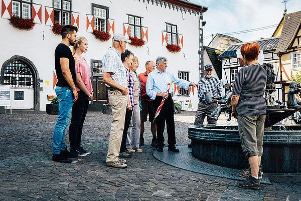 Gruppe Touristen im Sonnenschein vor dem historischen Rathaus und dem Ratsbrunnen die dem Gästeführer lauschen