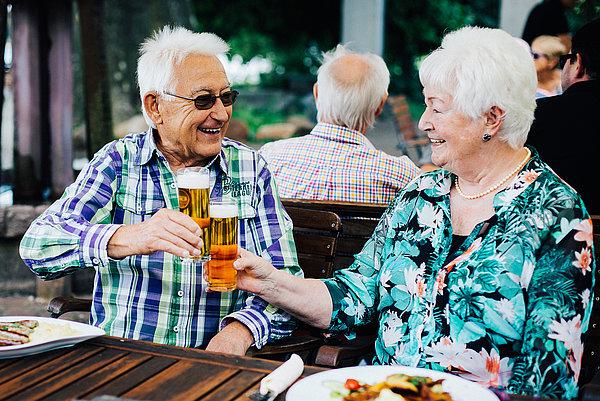 Glückliches Pärchen im Sommer beim Anstoßen mit Kölsch im Biergarten