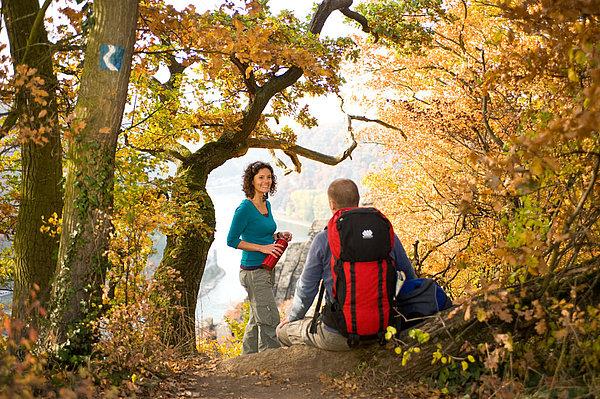 Paar bei der Rast im herbstlichem Wald mit Blick auf den Rhein