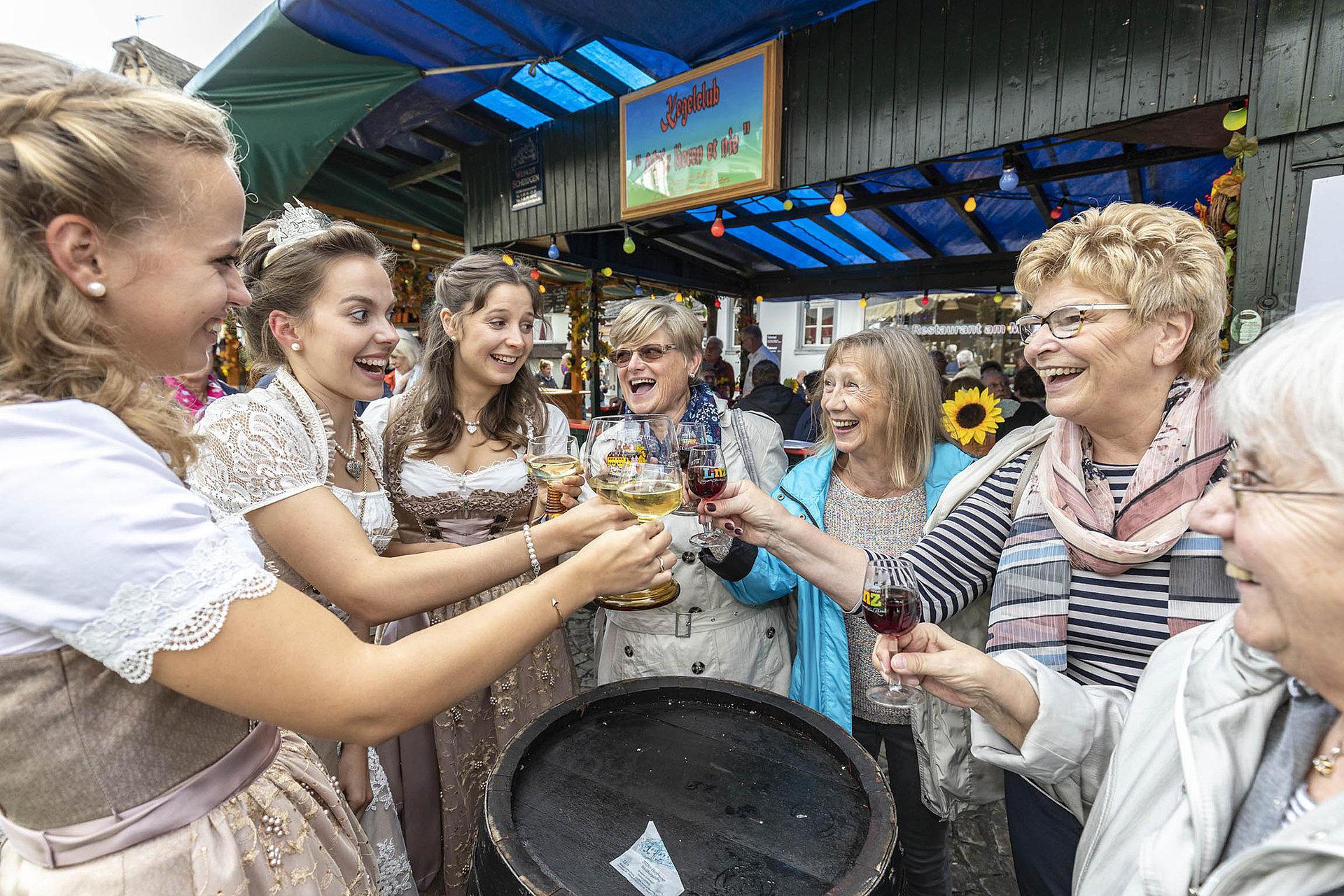 Linzer Weintrio beim Anstoßen mit lachenden Gästen im Linzer Weindorf