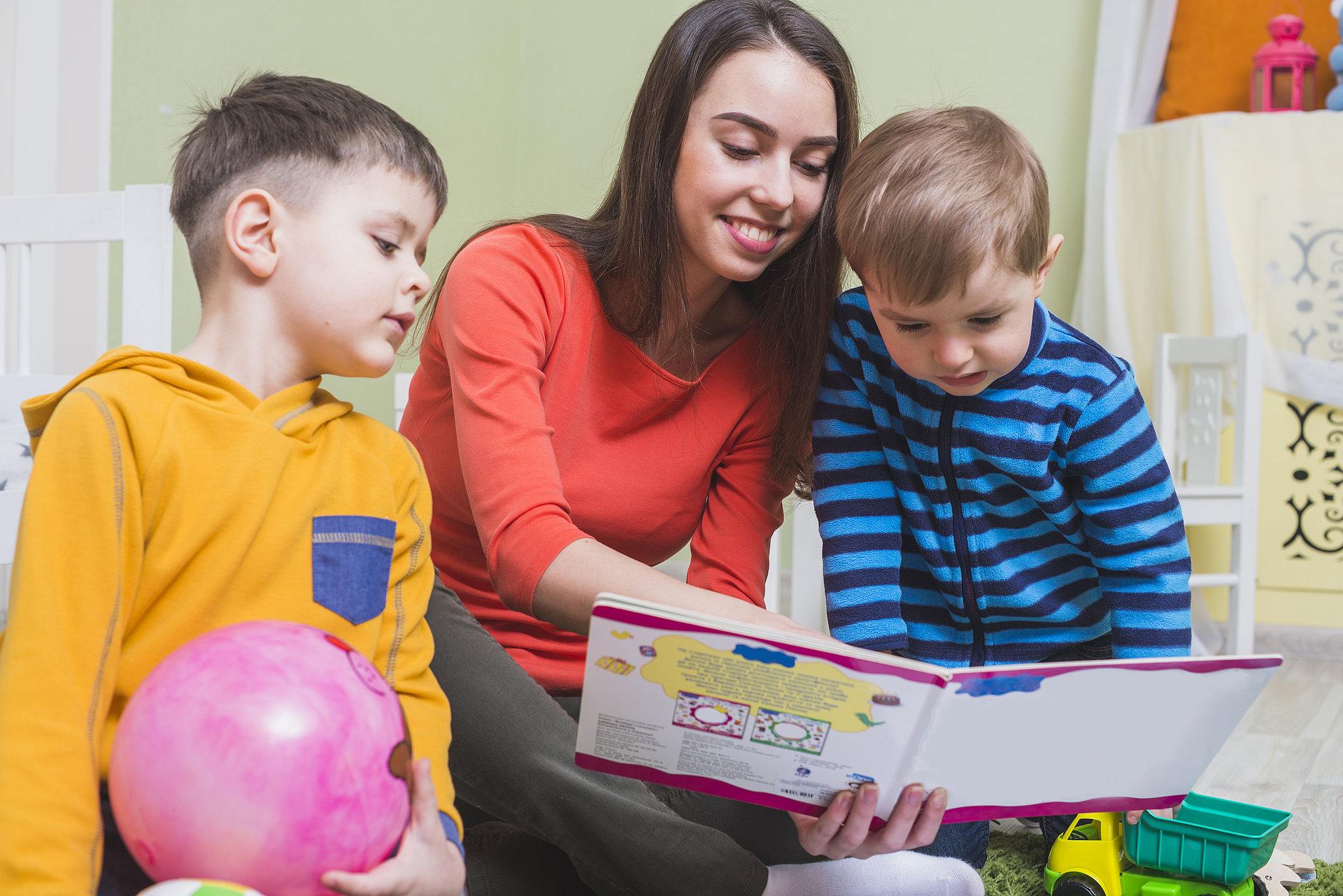 Kindergärtnerin beim Vorlesen mit zwei kleinen Jungs