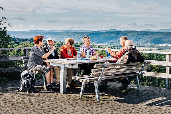 Gruppe Wanderer beim Picknick mit traumhafter Aussicht auf dem Linzer Kaiserberg