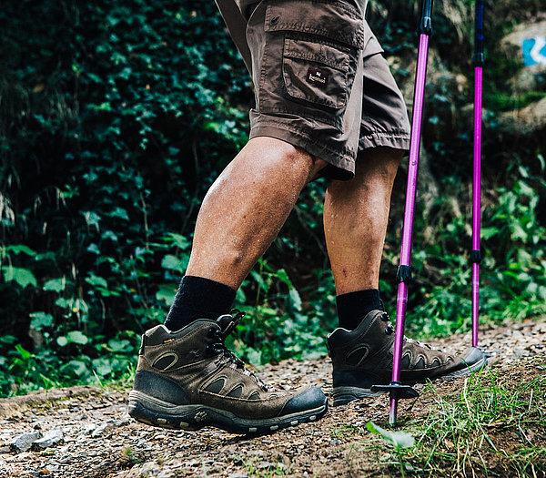Wanderschuhe in Bewegung, auf einem Wald-Schotter-Wanderweg